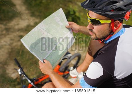 Handsome Bicyclist With Route Map On The Top Of Rock