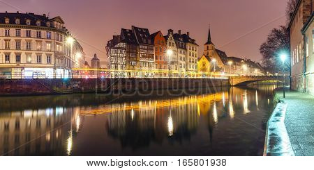Picturesque panorama of quay and church of Saint Nicolas with mirror reflections in the river Ile during morning blue hour, Strasbourg, Alsace, France