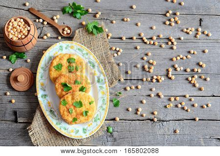 Roasted pea burgers on a plate. Vegetarian burgers made from peas and decorated with fresh parsley. Yellow dried peas scattered on a wooden table. Healthy meals without meat. Top view
