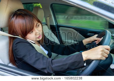 Portrait of Business woman using smart phone while driving a car