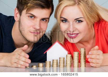 Young Smiling Couple Protecting Real Estate House Model With Stacked Tax Coins On Desk