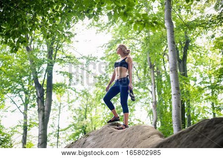 Woman Standing On The Top Of Rock After Climbing Boulder