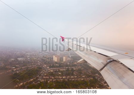 Adventure travel transport concept. View from plane window at sky with clouds wing and city