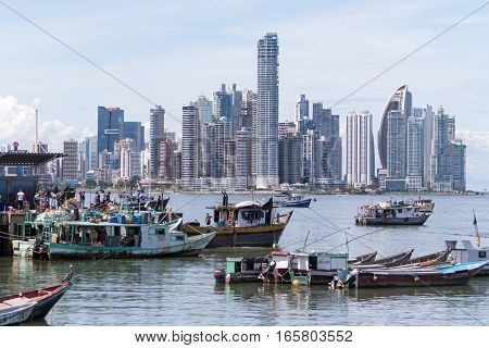 June 15, 2016 Panama City, Panama: small fishing boats floating on the water by the fish market with the modern downtown high-rise buildings in the background