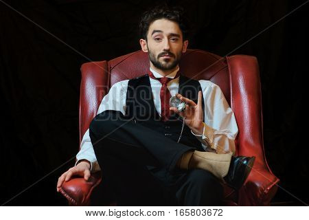 portrait of a young businessman with a pocket watch in a chair.