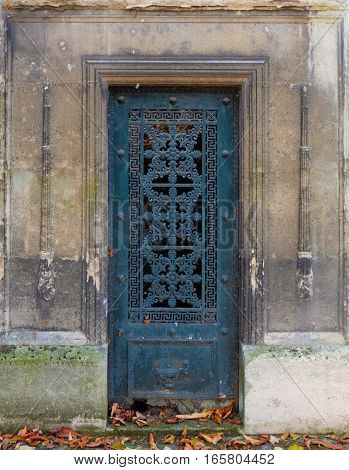 Blue steel door - an old and weathered iron entrance of an ancient tomb or crypt at a cemetery, ornate with geometric shapes and artistic curvy floral ornaments. The frames and borders are rectangle and chiseled into the stone casing. The metal door itsel