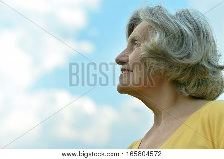beautiful mature woman, posing against blue sky with clouds