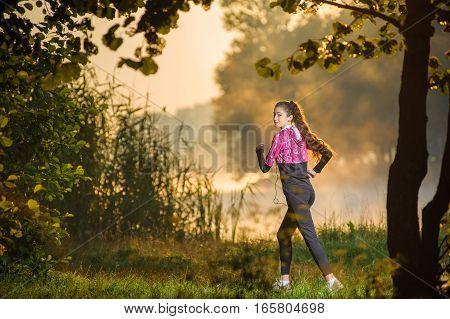 Female Runner Running In Nature During Sunrise