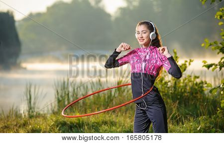 Girl Doing Hula Hoop Outdoors Near The Lake