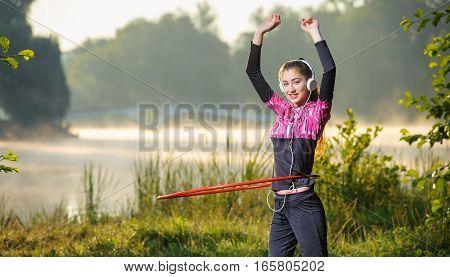 Girl Doing Hula Hoop Outdoors Near The Lake