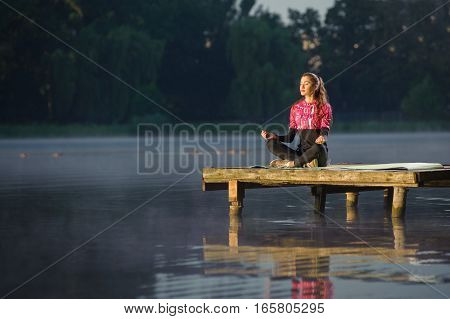 Woman Meditating In Nature On The River. Yoga