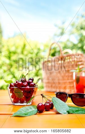 red cherry and glass of juice in the garden