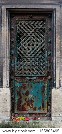 Old and rusty blue / turqoise steel rectangle door, decorated with small clover (quatrefoil) ornaments