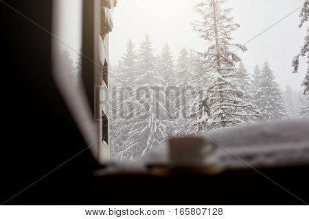 Mug with tea and coffee on the window sill snow in winter with a view of forest.