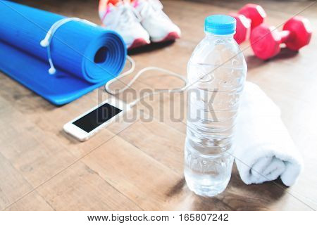 Bottle of water with towel and fitness accessories for woman background