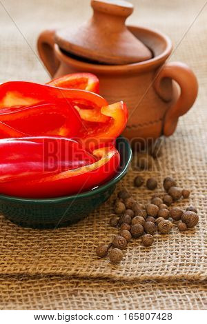 Sliced bell pepper in a dish and clay pot. Vertical food background with paprika and allspice.
