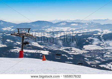 Chair lift on the top of ski slope. View of valley. Ski resort Kubinska Holal. Slovakia.