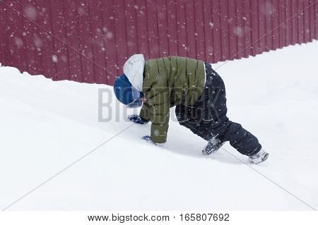 warmly dressed boy riding on a snowy hill