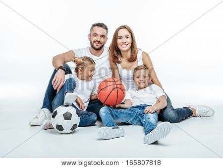 Cheerful family in white t-shirts and jeans sitting with soccer and basketball balls on white