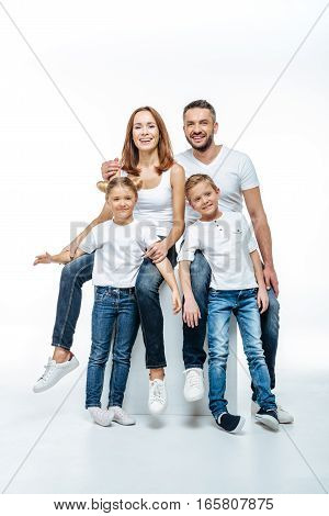 Happy parents with two children in white t-shirts and jeans having fun together and looking at camera