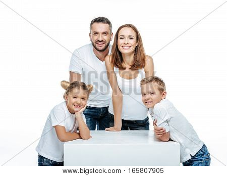 Happy family with two children standing together and looking at camera isolated on white