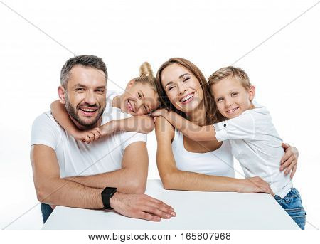 Smiling happy family in white t-shirts hugging