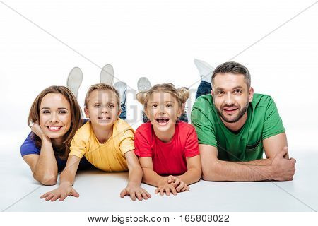 Happy family in colored t-shirts lying together and having fun on white