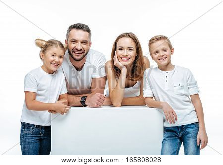 Cheerful family with two children standing together and looking at camera isolated on white