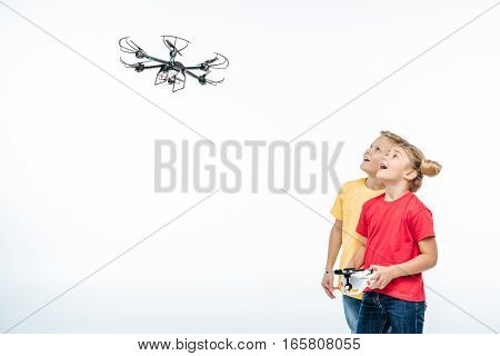 Happy kids playing with flying hexacopter drone isolated on white