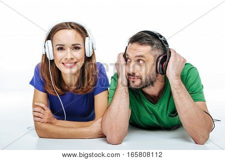 Couple in headphones and colorful t-shirts listening to music isolated on white