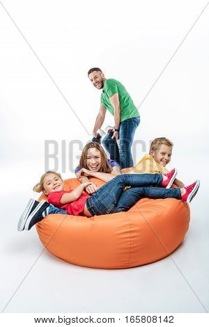 Happy family with two children having fun together in sack-chair isolated on white