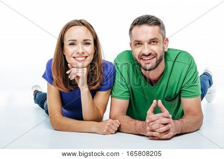 Beautiful couple lying and looking at camera with smile isolated on white