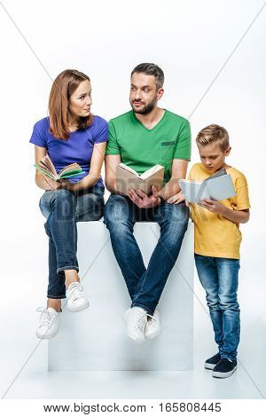 Happy family with one child reading books together on white