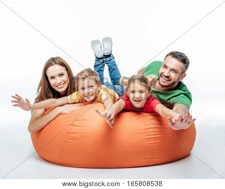 Happy family having fun together in sack-chair and looking at camera isolated on white