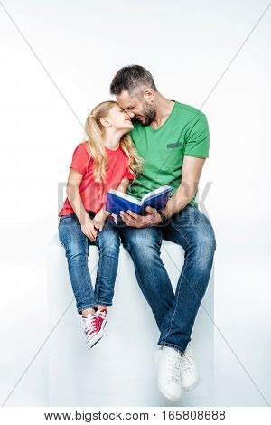 Happy father and daughter sitting with book and touching noses on white