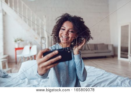 Pretty smiling african girl make selfie sitting on bed at home