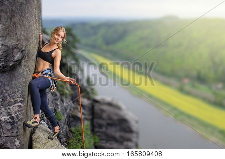 Female Extreme Climber Climbing Rock Over The River