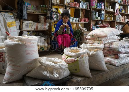 September 6, 2016 Silvia, Colombia: a young indigenous woman is knitting while waiting for customers in her convenience store located in the local market