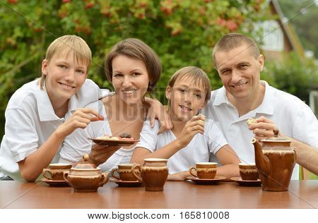 family drink tea together outdoors with sweets