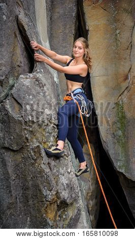Female Climber Climbing With Rope On A Rocky Wall