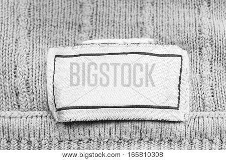 Blank white clothes label on white knitted background