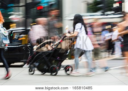 Young mother pushing the pushchair. Lots of people walking in Oxford street, London. Blurred image.
