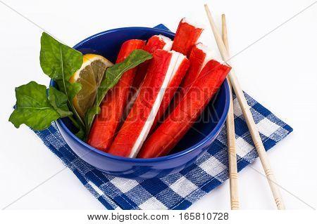 Surimi or crab sticks in blue salad bowl. Studio Photo