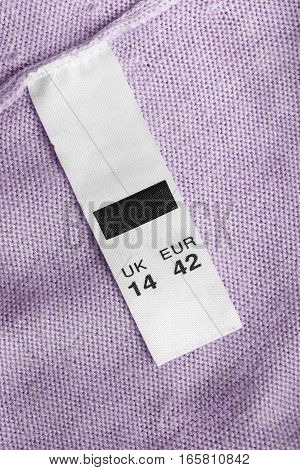Size clothes label on pink knitted cloth