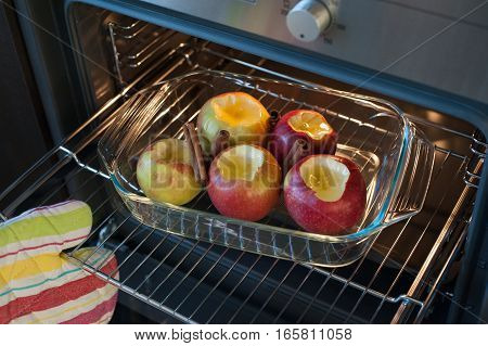 Preparing sweet dessert in the oven - five ripe apples with honey and cinnamon