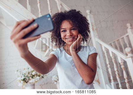 Beautyful african girl in white t-shirt make selfie using smartphone at home.