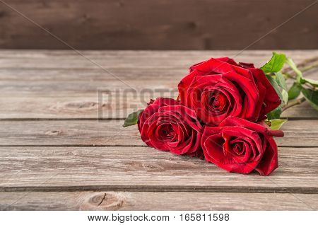 bouquet of red roses on wood background