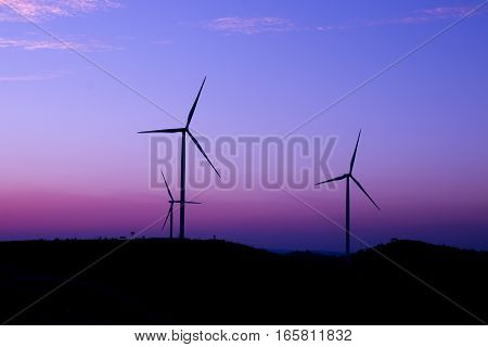 Wind Turbine silhouetted against a dramatic sunset sky.