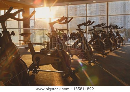 Modern gym interior with equipment. Fitness club with training exercise bikes in evening backlight.