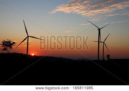 Wind turbine power generator at twilight .